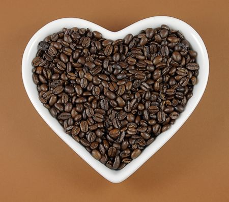 stimulated: roasted coffee beans in a white heart shaped dish Stock Photo