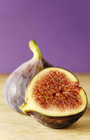 whole and half a fig on wooden chopping board