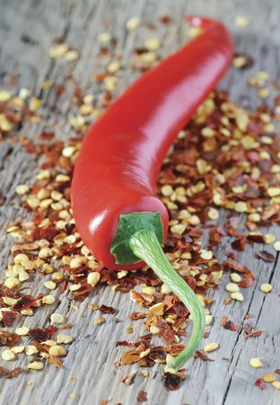 intense flavor: red chilli pepper resting on a bed of crushed chilli flakes Stock Photo