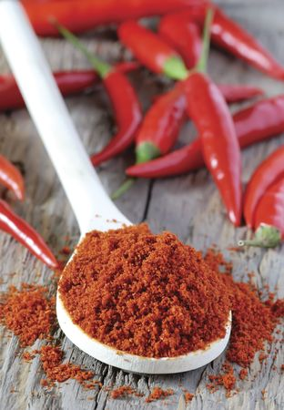 close up of spoon heaped with chilli powder with red chillies in background Stock Photo
