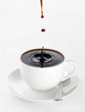 d�bord�: une tasse de caf� noir plein � ras bord avec les chutes jouant sur la surface menace de d�border. Banque d'images