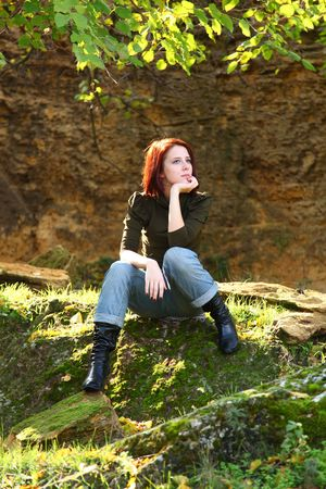 Girl sitting at stone in forst photo