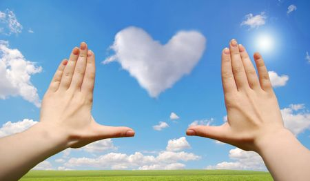 Frame made of hands over heart cloud over field photo