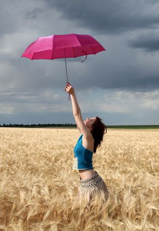 Girl with umbrella at field. photo