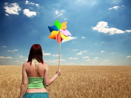 Girl with wind turbine at wheat field photo