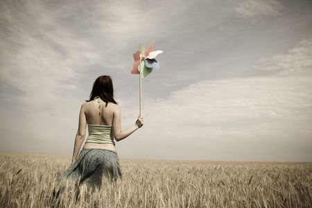 beauty farm: Girl with toy wind turbine at field in retro style  Stock Photo