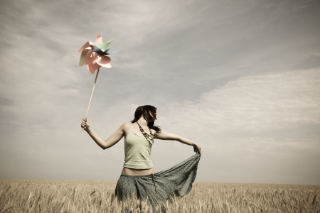 Girl with toy wind turbine at field in retro style Stock Photo - 7500285