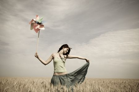 Girl with toy wind turbine at field in retro style  Stock Photo
