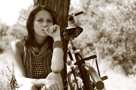 Beautiful girl sitting near bike and tree at rest in forest. Photo in retro style.  photo