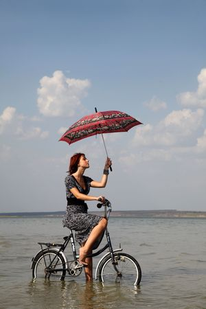 surrealism: Girl go for a cycle ride at water with umbrella in hand.  Stock Photo