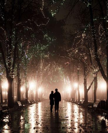 banc de parc: Couple de marcher � alley dans les lumi�res de la nuit. Photo prise en style vintage.  Banque d'images