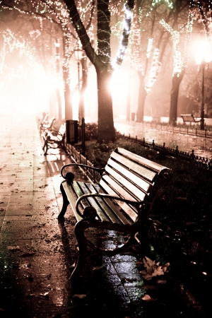 Bench in night alley with lights in Odessa, Ukraine. Photo in retro style. Stock Photo