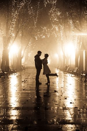 Couple walking at alley in night lights. Photo in vintage style.  Stock Photo