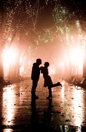 Couple walking at alley in night lights. Photo in vintage style.  photo