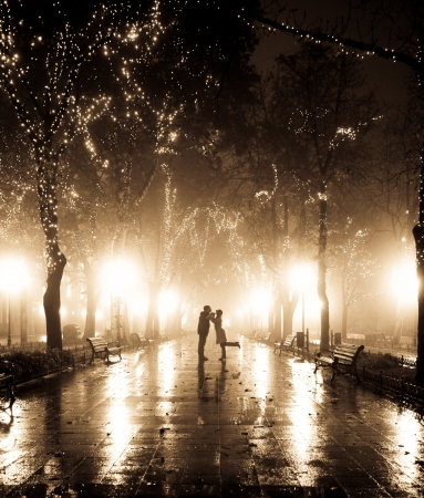 Couple walking at alley in night lights. Photo in vintage style. Stock Photo - 7500351