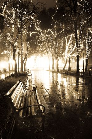 Bench in night alley with lights in Odessa, Ukraine. Photo in retro style.  photo