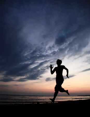 Runner on the beach at sunset Stock Photo