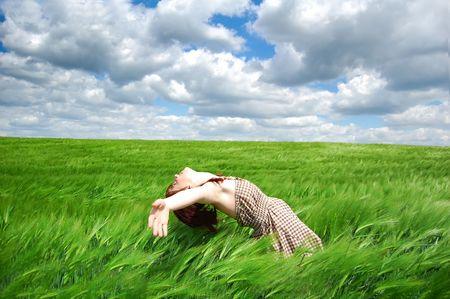 Beautiful young girl lying at green field photo