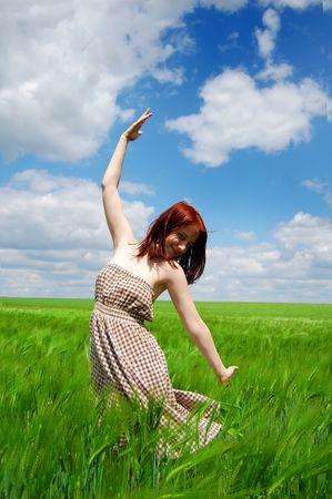 Beautiful young girl at green field photo