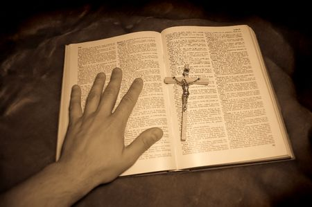 book with crucifixion and hand photo