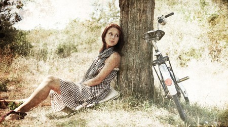 Beautiful girl sitting near bike and tree at rest in forest Stock Photo - 7514095