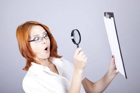 Young businesswomen with white plan board and loupe. Stock Photo - 7512676