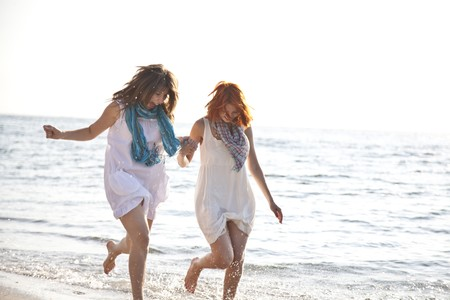 Two beautiful girls running on the beach. photo