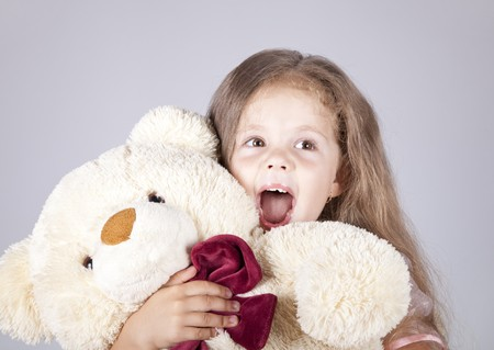 Little shouting girl embraces bear cub. photo