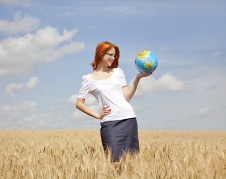 Young Businesswomen in white keeping globe in hand at wheat field photo