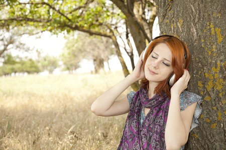 Young  smiling fashion with headphones near tree. photo