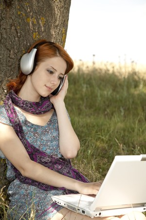 Young smiling fashion girl with notebook and headphones sitting near tree. photo