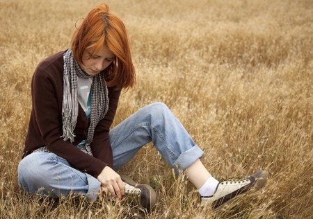 upset woman: Lonely sad red-haired girl at field