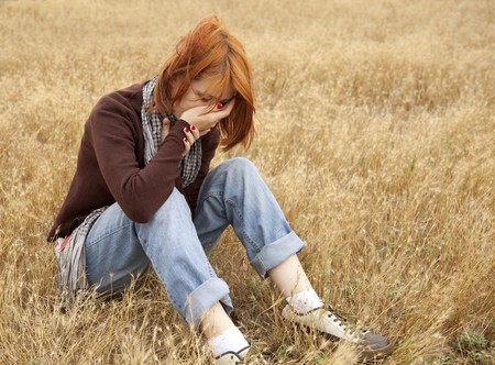 Lonely sad red-haired girl at field Stock Photo - 7537271