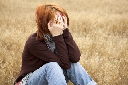 country girls: Lonely sad red-haired girl at field