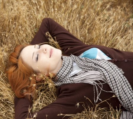 respite: Young beautiful girl lying at yellow autumn field. Stock Photo