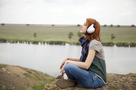 Young fashion girl with headphones at rock near lake. photo