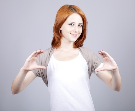 addle: Red-haired businesswoman show something in air.