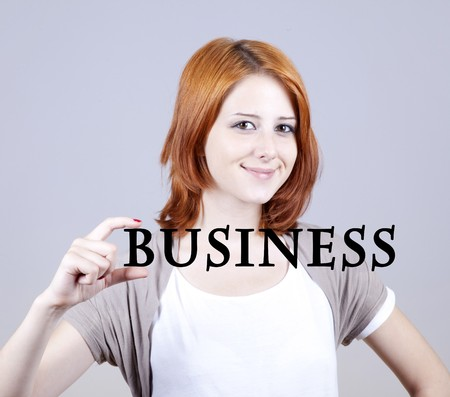 addle: Red-haired businesswoman show abstract word businiess. Stock Photo