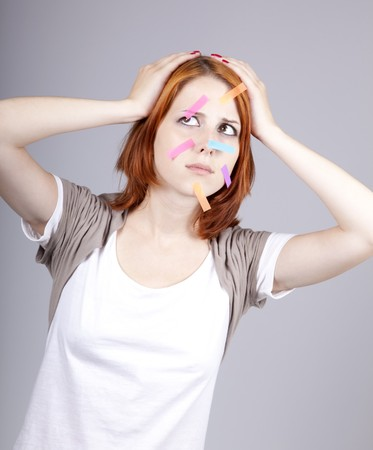 Confused red-haired businesswomen with notes on face. photo