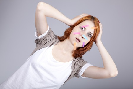 addle: Confused red-haired businesswomen with notes on face. Stock Photo