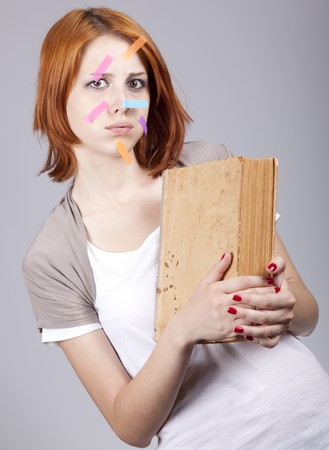 addle: Red-haired businesswoman with book and notes on face.  Stock Photo