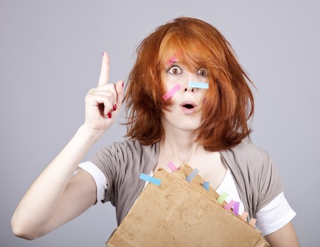 Red-haired businesswoman with book and notes on face.  photo