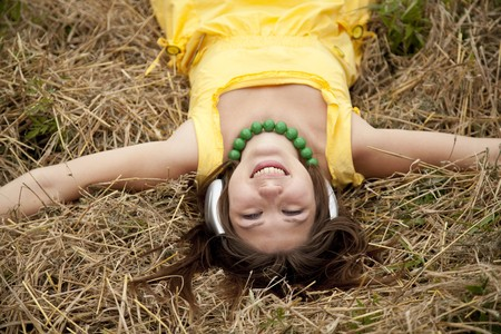Young beautiful girl in yellow with headphones at field. photo