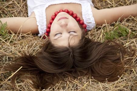 hay field: Bella ragazza sdraiata al campo di fieno.  Archivio Fotografico