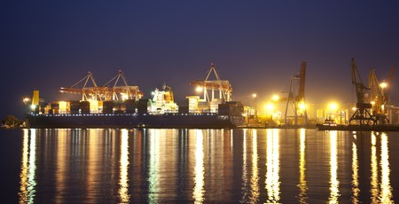 Cargo ship in the port at night photo