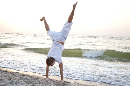 Young man doing cartwheels on the beach Stock Photo - 7594074