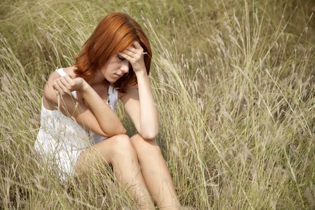 Sad red-haired girl at grass. photo