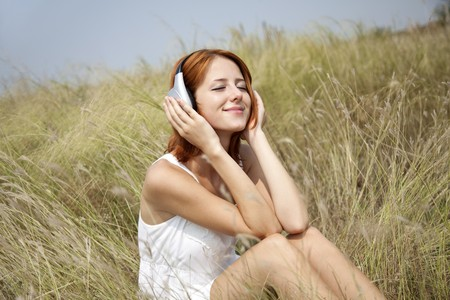 Beautiful red-haired girl at grass with headphones. photo