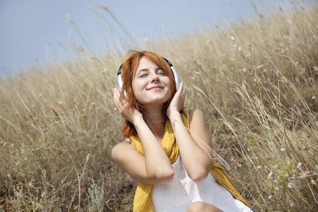 Beautiful red-haired girl at grass with headphones.