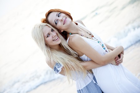 Two beautiful young girlfriends on the beach of Black Sea. Sea and sunlight is on background.  photo